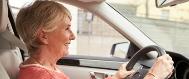 In car view of senior female driver at the wheel of a car